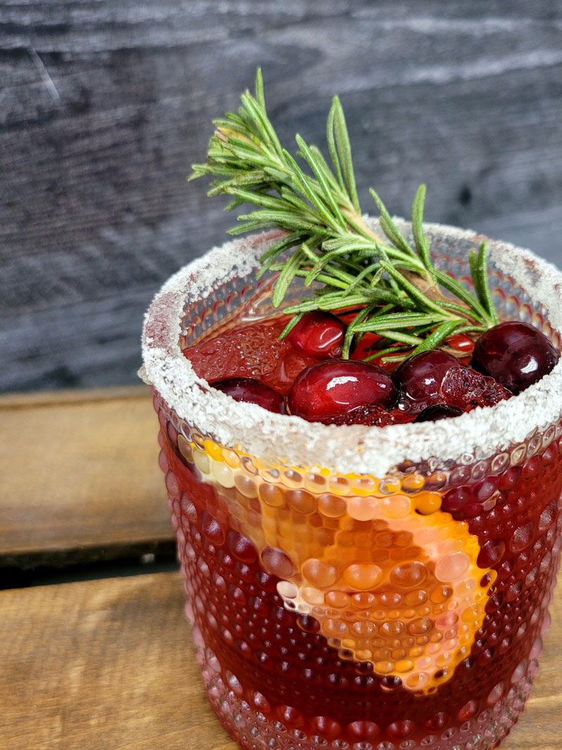 merry merry margarita, a red cocktail garnished with rosemary, cranberries, and an orange slice